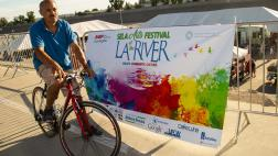 Festivalgoer cycles past sign advertising the SELA Arts Festival.