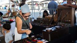Woman browses bracelet selection on display.