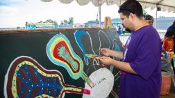 Festivalgoer painting a guitar at one of the festival's interactive exhibits.