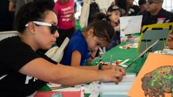 Guests create crafts at table booth.