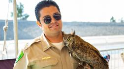 Los Angeles Conservation officer holds owl.